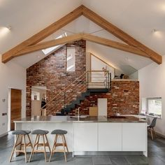 Barn renovation and conversion, with green oak frame truss, white unit and stainless steel island kitchen, reclaimed red brick feature wall, and steel staircase Brick Accent Walls, White Brick Walls, Oak Framed Extensions, House Extensions, Scissor Truss, Brick Feature Wall, Roof Truss Design, Decoracion Vintage Chic, Converted Barn