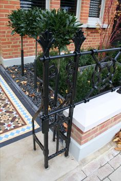 Stylish, black railings and contemporary bushes in London front garden.