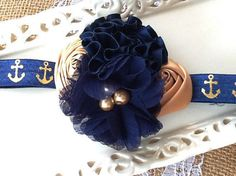 Navy Chiffon and Navy Satin Flower with Gold Rolled Satin Flower Buds are featured on this Newborn Baby or Adult Headband on a 5/8 inch Navy with Gold Anchor adjustable band    The Headband that grows with your child!    Measures 4 inches across    Fits sizes Newborn to Adult    Custom orders, I do enjoy creating these, if you have an outfit that you would like to have a special piece made for, don't hesitate to ask me, send me a picture and we can work together to create something special…