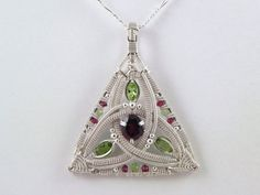Faceted garnet and peridot sterling argentium silver wire wrap pendant. $400.00, via Etsy.