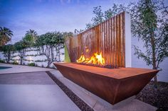 A rusted corrugated metal fence serves as a backdrop to this dramatic fire pit. The rectangular pit has a rusted-metal look that provides stark contrast to the light-colored fence and patio while complementing its metal-fence backdrop.