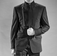 The Bib Front Jacket is a single breasted men's suiting jacket with structure detail on the arms and a zipped, assymetrical bib feature with contrasting material at the collar. The bib can be worn open, revealing the contrasting material, or zipped up for a high neck. The cuffs are finished with zip detail.