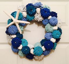 Beach Cottage Pinecone Zinnias Wreath. Each wreath will be painted in Oceanic colors and will is reminiscent of a real zinnia flowers. Each Pinecone is descaled and hand cut, painted and then wired upside down to look like a Zinnia. Inside each Pinecone Zinnia is a faux pearl and