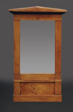 A small Biedermeier mirror German, 19th cent. Fruittree wood with rootwood, veneered. With ornaments of ebonised accents. Partly traces of age. H. 74,5 cm, w. 42 cm.
