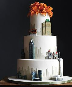 Chocolate-hazelnut cake covered in fondant and topped with flowers made of gum paste; buildings are made from modelling chocolate.   by For the Love of  Cake, Canada