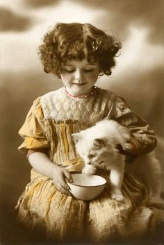 Little girl with a bowl, and her white cat.