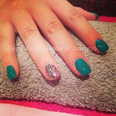 Acrylic nail extensions with glitter ring finger design.