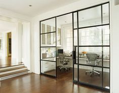 """""""Sliding glass-and-steel doors echo the windows and close off the study area. An Aeron chair stands at each workstation."""" Photo by Pieter Estersohn. Interior design by Sally Markham. House Beautiful (December 2006)."""