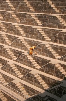 """Nelson Oliver: """"Chand Baori Temple and Stepwell. The woman here in her orange sari sweeps the dust downward step by step in the midday sun."""""""