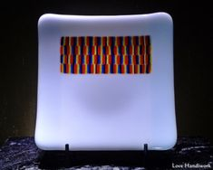 This is a (approximately 5 square slumped fused glass dish. This is a two-tone white plate with a multi-coloured stripe rectangle near the top of it. This piece is food safe. Bottle Slumping, Glass Beer Mugs, Getting Fired, Square Plates, White Plates, Glass Dishes, Safe Food, Fused Glass, Liquor