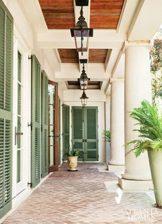 Brick floor porch with green shutters and iron lanterns.