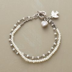"Our exclusive two-strand bracelet intermingles cultured freshwater pearls with sterling links and seed beads. A mother of pearl heart dangles from the toggle clasp. Approx. 7-1/2""L."