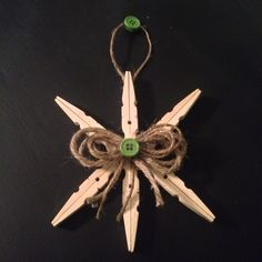 Clothespin Christmas snowflake ornament (clothepins, jute, buttons, hot glue) 1. Take apart 6 clothespins 2. Hot glue them back to back 3. Assemble 6 pieces in hexagon pattern 4. Create a jute bow and hanger 5. 1 button on bow center (I used two back to back at top)