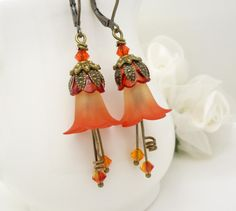 Lovely bright orange lucite flower earrings, with shades of peach and burnt orange . Handmade jewelry by WickedRuby.  These earrings were made using: ~ Flame orange lucite flowers ~ Bright orange swarovski crystals ~ Antique bronze beads and ear wires  The earrings measure 2 1/8 inches from top to bottom  Thanks for stopping by to view my orange flower earrings To see more of my vintage and gothic inspired jewelry visit my store: http://www.etsy.com/shop/wickedruby  A...