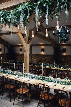 Image by Samuel Docker Photography - Natural barn wedding decorations - Hanging foliage garlands - candles and greenery garlands table decor