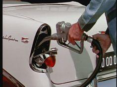 Gas station attendant filling up a 1956 Chevrolet Bel-Air.  Hidden fuel filler, gas cap.