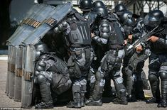 Wall: Paramilitary riot police personnel drill with the rapid deployment riot unit for major events and the aerial support unit at their headquarters in Rio de Janeiro, Brazil, yesterday