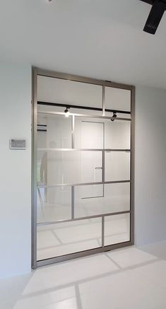 """Glass pivot door finished in a very special """"stainless steel"""" anodized aluminium. The pivot hinge is fully intergrated inside the door! There's nothing that needs to be installed in advance criativas sala com espelho Glass pivot door stainless steel Room Divider Doors, Office Room Dividers, Pivot Doors, Entry Doors, Glass Partition, Partition Door, The Doors, Front Door Design, Glass Design"""