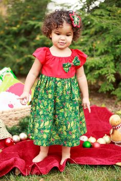 Red holly Christmas dress made from soft 100% cotton. The red bodice has short sleeves and the full skirt is made from a complementary green