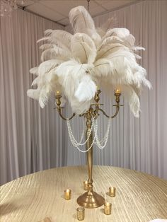 White feathers, candelabra, the pearls will be removed. This will be on black table cloth with gold sequin runner. Very elegant and will add gold and cream holiday balls.