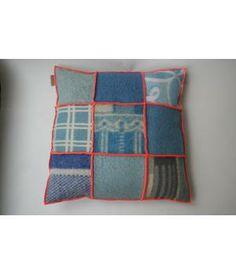 Groot kussen bekleed met blauwe wollen dekens uit de jaren 70 en afgewerkt met een frisse neon-oranje locksteek. Het resultaat:een nostolgisch aaibaar kussen met hippe accenten van nu. Hebben&Houden via metdehand.nl