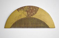 Antique Japanese  comb lacquered in gold with applied red flowers further painted in gold.  The flowers may be a type of  Campanula  ?glomerata?  very light weight wood comb.