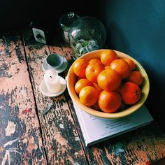 Bowl of oranges on old, antique, rustic, weathered, painted table. Black, orange, white.