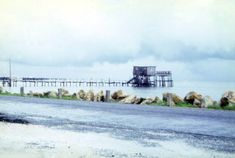 "View showing the ""Thomas guest house"" at the end of a pier off 1st St. in Cedar Key, Florida - The stilt house, also known as ""Honeymoon Cottage"", was built in 1959. It was mostly destroyed during Hurricane Elena in 1985"