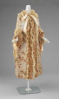 Evening Cloak - 1885-1889, French - The Metropolitan Museum of Art - The chinoiserie print covered in the vermiculate gold chainstitch alongside the contrasting embroidered net trim encompasses the wearer in lavish exoticism. It was fashionable in the period to seek such exoticism in home furnishings as well as fashion. The design vocabulary of the world was often reinterpreted in embroidery styles throughout the period.