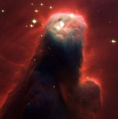 This photo from NASA's Hubble Space Telescope shows an ominous pillar of gas and dust known as the Cone Nebula. The image shows the top portion of the nebula that is 2.5 light years in height. The Cone Nebula is 2,500 light-years from Earth in the Monoceros constellation. The red halo of light seen around the pillar is caused when ultraviolet radiation causes hydrogen gas in the nebula to glow.