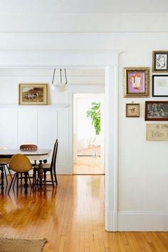 honey-tone wood floors, eclectic chair grouping, and a varied gallery wall arrangement is all pulled together by a tasteful use of white walls and white trim