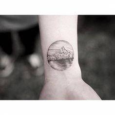Fine line iceberg circle tattoo on the inner wrist.
