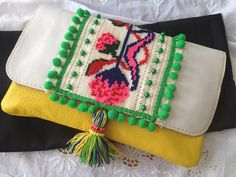 clutch purse with bobble trim, clover embroidery and tassel
