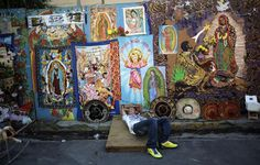A street vendor lays next to religious merchandise portraying the Virgin of Guadalupe near the Basilica de Guadalupe in San Salvador on 12 December 2012. (Photo: AFP - Jose CABEZAS)