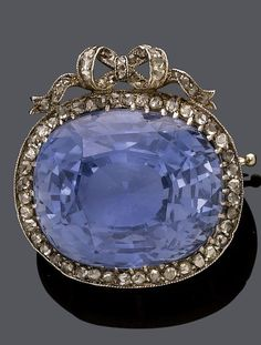 AN ANTIQUE SAPPHIRE AND DIAMOND BROOCH, PROBABLY RUSSIAN, CIRCA 1900. Featuring an oval Ceylon sapphire weighing 28.19 cts, surrounded by rose-cut diamonds, surmounted by a diamond-set bow motif, mounted in silver and rose gold, with maker's marks AH on the needle. #antique #Russian #brooch