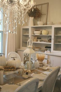 all white dining room decorated for thanksgiving.