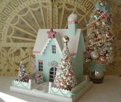 This lovely mint colored house is so bright and cheery with its snow dusted roof and pink Dresden trim. A puff of Smoke escapes from the chimney,