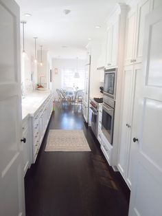Cococozy: The eat in galley kitchen in Carlyn Henry's home features dark wood floors and cabinets and walls painted in Benjamin Moore's Simply White. (above)