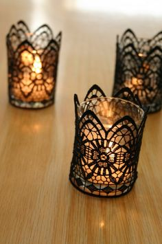 Pick up a yard or two of black lace trim, cut off a strip that covers the perimeter of your votive candle. Using a needle and black thread, overlap the edges and make small stitches to tack in place.