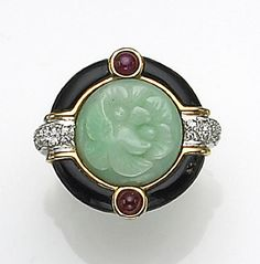 A jadeite jade, diamond, ruby, black onyx and eighteen karat gold ring centering a round jadeite disk carved to depict a rose, framed by black onyx, the compass points set with round ruby cabochons and round brilliant-cut diamonds, on a gold mount.