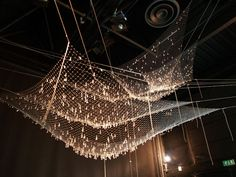 "Ingo Maurer installation at Spazio Krizia in 2009.  ""Tears of the Fisherman"". Three nets suspended across a room are embedded with Swarovski crystals.  The light source can be dimmed and is attached to a pendulum making it swing and sway. Bet it was stunning."