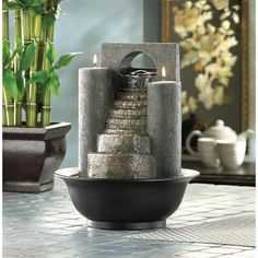 Eternal Steps Fountain - Fire and water combine to form one spectacular decoration! Cascades of water trickle down faux-stone steps, while tealights glimmer from atop twin pillars. A tabletop fountain to treasure!