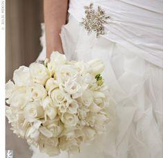 round bouquet of white roses, freesia, French tulips, and gardenias.
