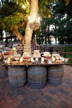 Outdoor dining....love the barrels used to support the table!