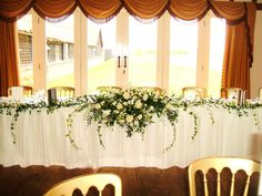 Long and low top table arrangement, wedding, ivory, trailing ivy, white Naomi rose, stocks, antirrhinum, hard ruscus.