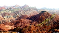 The mountains are part of the Zhangye Danxia Landform Geological Park in China. Layers of different colored sandstone and minerals were pressed together over 24 million years and then buckled up by tectonic plates