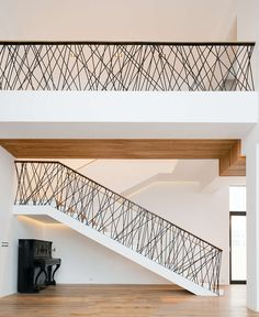 This home designed by Monoloko Design, features custom railings on the stairs and the top floor, made from randomly placed steel supports that have been powder coated black