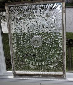 An old window decorated with broken and cut glass, glass gems and shapes.