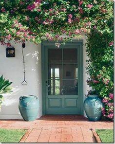 Porta envidraçada emoldurada por uma trepadeira florida