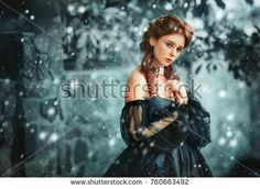Winter portrait of a beautiful red haired girl in gothic black style. Pretty young princess and queen under snowflakes. Cold Art work.